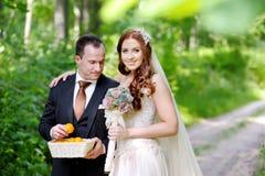 Junge Braut und Bräutigam, die einen Spaziergang macht Stockbild