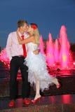 Braut- und Bräutigamkuß nahe rosa Brunnen Lizenzfreies Stockbild