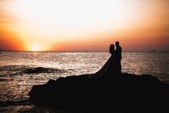 Junge Braut und Br?utigam der reizenden Paare auf Sonnenunterganghintergrund Sch?ner Himmel stockfoto