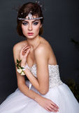 Junge Brautfrau im Hochzeitskleid auf grauem Hintergrund Stockbild