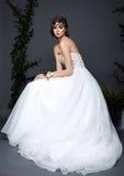 Junge Brautfrau im Hochzeitskleid auf grauem Hintergrund Lizenzfreie Stockfotografie