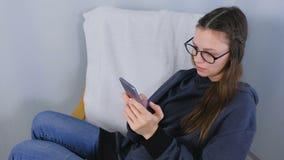 Junge brunette Frau in den Gläsern schreibt eine Mitteilung an einem Handy, der zu Hause im Lehnsessel sitzt stock video footage