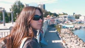 Junge brunette Frau in der Sonnenbrille, die das Meer im Herbst betrachtet stock footage