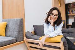 Junge brunette Frau des Porträts in den schwarzen Gläsern, die auf Couch in der modernen Wohnung kühlen Bequem, frohe Stimmung stockfotos