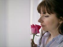Junge brunette Frau, die eine Rose bereitsteht das Fenster schnüffelt lizenzfreies stockbild
