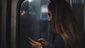 Junge brunette Frau, die irgendwo in bewegliche Untergrundbahn geht Mädchen, das den Smartphone steht nahe dem Fenster auf Sonnen stock video footage