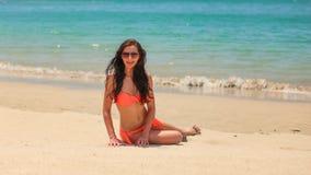 Junge brunette Frau im Bikini und in Sonnenbrille, sitzend auf Sandstrand, ruhiger azurblauer Seehintergrund lizenzfreies stockfoto