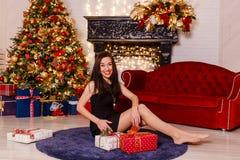 Junge brunette Frau im kurzen schwarzen Kleid, das auf dem Teppich nahe dem Weihnachtsbaum sitzt Lachende junge Frau Schöne Frau stockfoto
