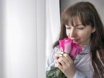 Junge brunette Frau schnüffelt einen Blumenstrauß von den Rosen, die das Fenster bereitstehen stockfotografie