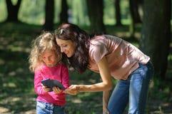 Junge Brunette-Mutter zeigt, wie man Smartphone zu ihrem blonden Kind verwendet, das warmen Sunny Weather Outside in genießt Stockfotos