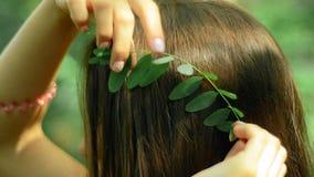 Junge Brunetteeinsätze in den Blättern in das Haar im Wald stock video