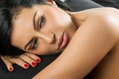 Junge Brunettefrau auf dem Bett, schwarzes Blatt des Hintergrundes Stockfoto