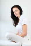 Junge Brunettefrau in der weißen Ausstattung auf einem weißen Sofa mit Blickkontakt Lizenzfreies Stockfoto