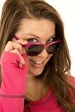 Junge Brunettefrau, die über ihrem Sonnenbrillelächeln blickt Stockbilder