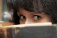 Junge Brunettefrau, die altes Buch liest Stockfotografie