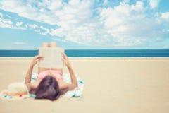 Junge Brunettefrau, die auf dem Strand liest ein Buch liegt Stockfotos