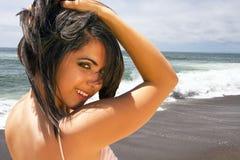 Junge Brunettefrau, die auf dem Strand vacationing ist Stockbilder