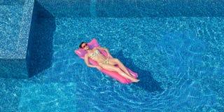 Junge Brunettefrau, die auf rosa Matratze im Swimmingpool Nickerchen macht Stockfotografie