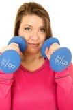 Junge Brunettefrau, die Blau 8 Pfund Barbells kein Lächeln halten steht Stockbild