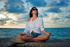 Junge Brunettefrau, die durch den Ozean bei Sonnenuntergang meditiert Stockfotografie