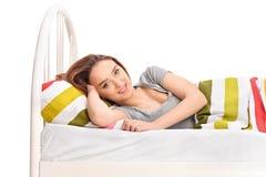 Junge Brunettefrau, die in einem Bett liegt Lizenzfreies Stockbild