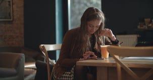 Junge Brunettefrau, die am Telefon beim Sitzen im Restaurant schreibt Lizenzfreie Stockfotografie