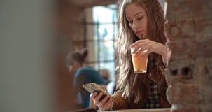 Junge Brunettefrau, die am Telefon beim Sitzen im Restaurant schreibt Lizenzfreies Stockfoto