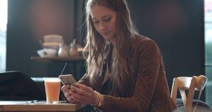 Junge Brunettefrau, die am Telefon beim Sitzen im Restaurant schreibt Stockfoto