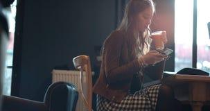 Junge Brunettefrau, die am Telefon beim Sitzen im Restaurant schreibt Stockfotos