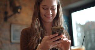 Junge Brunettefrau, die am Telefon beim Sitzen im Restaurant schreibt Stockbilder
