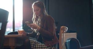 Junge Brunettefrau, die am Telefon beim Sitzen im Restaurant schreibt Lizenzfreies Stockbild
