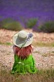 Junge Brunettefrau, die vor violettem Lavendelfeld I sitzt Lizenzfreie Stockfotos