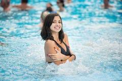Junge Brunettefrau in einem schwarzen Badeanzug mit einem schneeweißen Lächeln in einem Swimmingpool mit Jacuzzi Lizenzfreie Stockfotos