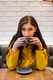Junge Brunettefrau in einer Kaffeehüftenkaffeestube einen Cappuccino trinkend lizenzfreies stockbild