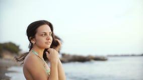 Junge Brunettefrau im Bikini, der Abstand untersucht und auf Seehintergrund träumt stock video