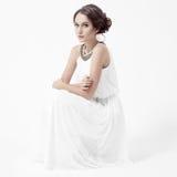 Junge Brunettefrau im weißen Kleid. Weißer Hintergrund. lizenzfreies stockfoto