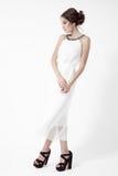 Junge Brunettefrau im weißen Kleid. Weißer Hintergrund. stockbild