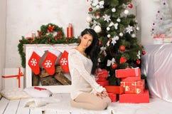 Junge Brunettefrau im Weihnachtsinnenraum lizenzfreies stockfoto