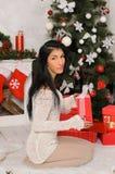 Junge Brunettefrau im Weihnachtsinnenraum lizenzfreie stockfotos