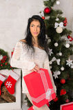 Junge Brunettefrau im Weihnachtsinnenraum stockfoto