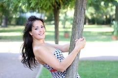 Junge Brunettefrau ist in einem Park entspannend Stockbilder