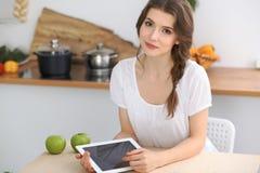 Junge Brunettefrau kocht in der Küche Hausfrau wählt das beste Rezept unter Verwendung des Berührungsflächencomputers Konzept von Stockfotos