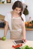 Junge Brunettefrau kocht in der Küche Hausfrau wählt das beste Rezept unter Verwendung des Berührungsflächencomputers Konzept von Stockfotografie