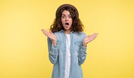 Junge Brunettefrau mit dem gelockten Haar öffnete ihren Mund in einer Überraschung, über gelbem Hintergrund lizenzfreie stockfotografie