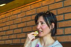 Junge Brunettefrau mit dem kurzen Haar etwas Gebäck essend Stockfotos