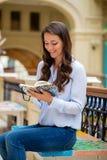 Junge Brunettefrau mit einem Notizbuch lizenzfreie stockbilder