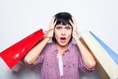 Junge Brunettefrau mit Einkaufenbeuteln Stockfotografie