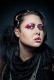 Junge Brunettefrau mit Modemake-up auf Dunkelheit Stockbilder