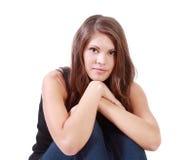 Junge Brunettefrau sitzt mit seinen Händen auf verbogenen Knien Lizenzfreie Stockfotografie