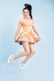 Junge Brunettefrau Smilling im orange Kleid, das auf blauen Hintergrund springt Stockfotos